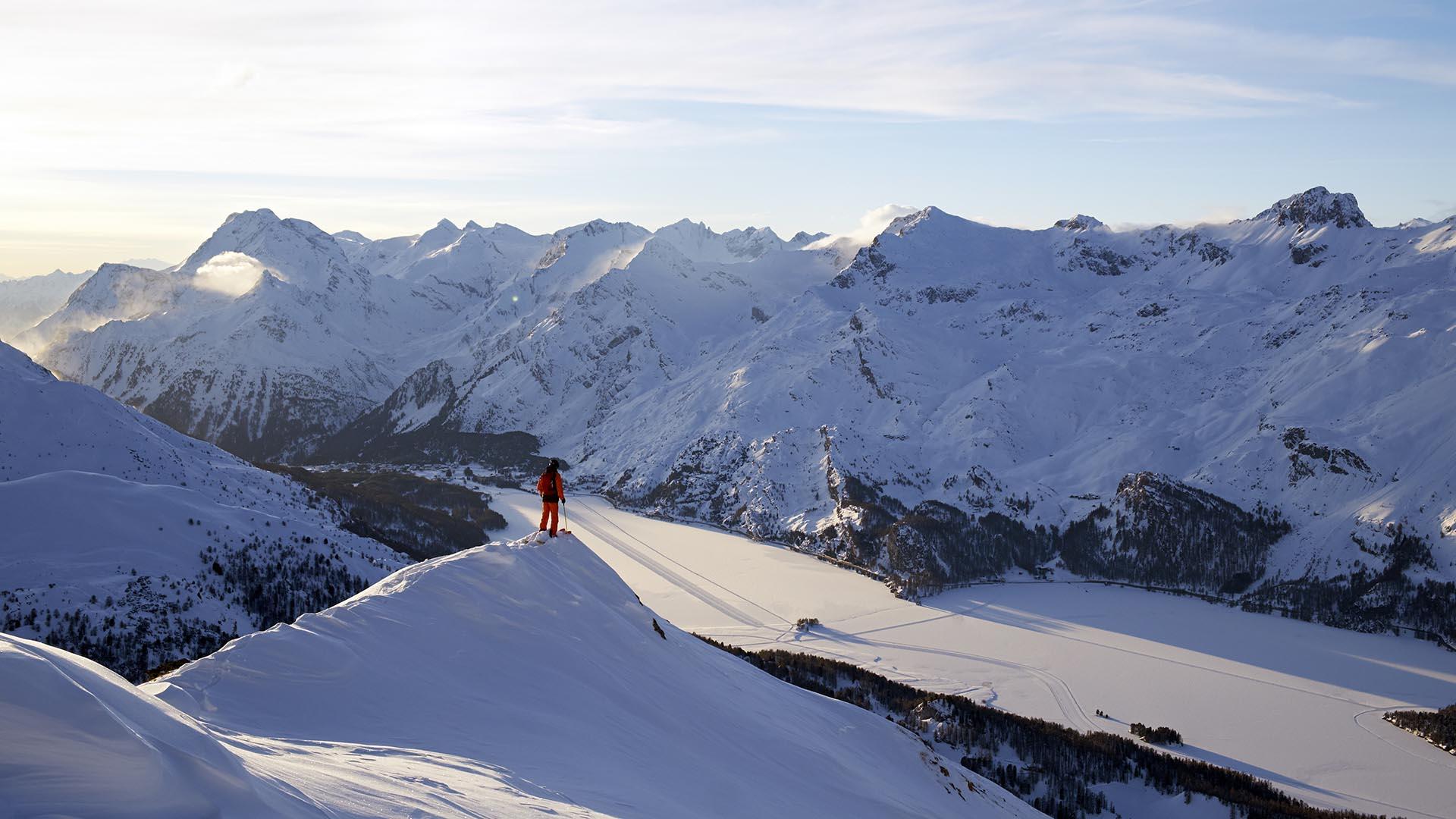 ENGADIN ST. MORITZ - Freerider im Skigebiet Corvatsch/Furtschellas unterhalb des Piz Grialetsch bei der Abenddaemmerung. Im Hintergrund die Ortschaft Maloja und der gefrorene Silsersee.